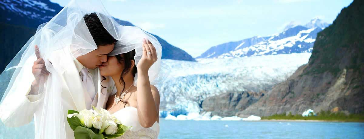 Wedding couple kiss in front of Mendenhall Glacier