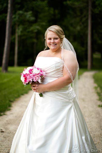 Bride poses along gravel driveway in Cass Lake, Minnesota