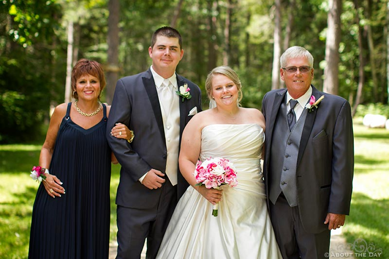 Bride and Groom with her parents  pose along gravel driveway in Cass Lake, Minnesota
