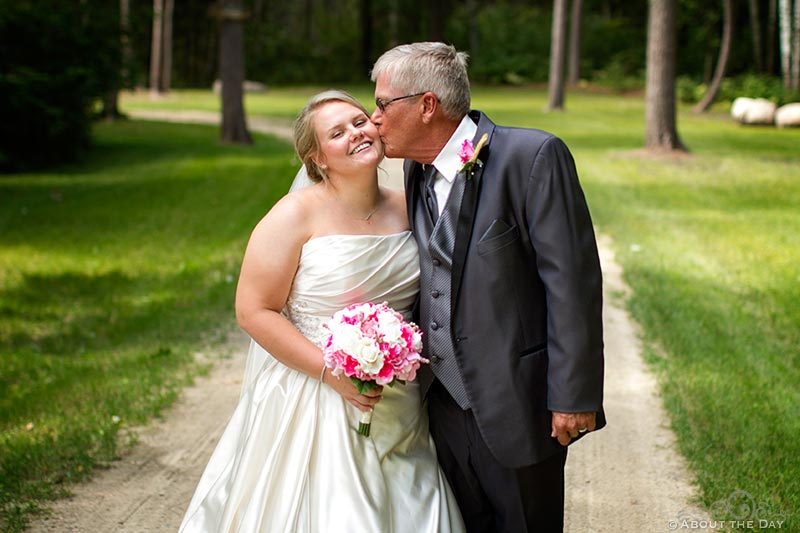 Father kisses bride on the cheek along gravel driveway in Cass Lake, Minnesota