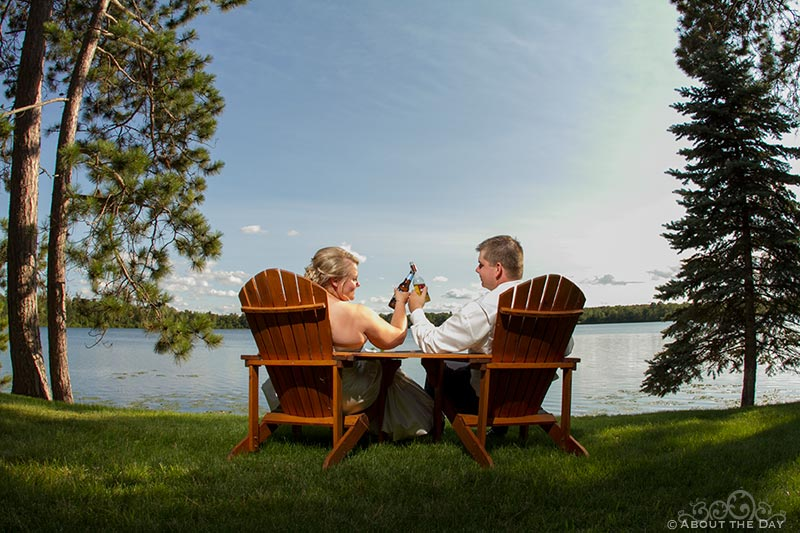 Wedding couple relax in chairs at sunset near Cass Lake, Minnesota