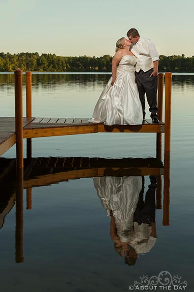 Bride and Groom kiss on the dock at sunset near Cass Lake, Minnesota