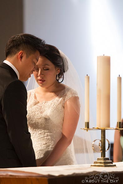 Bride and Groom pray during unity candle service