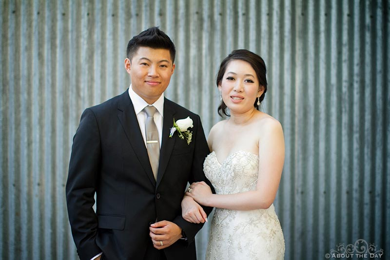 Bride and Groom stand in front of metal shed at Hurst Ranch