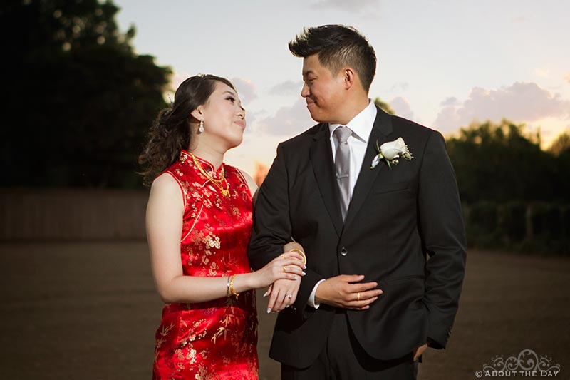 Bride in a red asian dress stands with Groom at sunset at Hurst Ranch