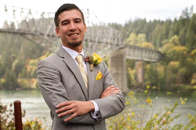 Groom poses in front of the Bridge of the Gods