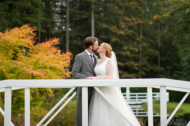 Bride and Groom kiss on white bridge at Natures Connection in Arlington, Washington