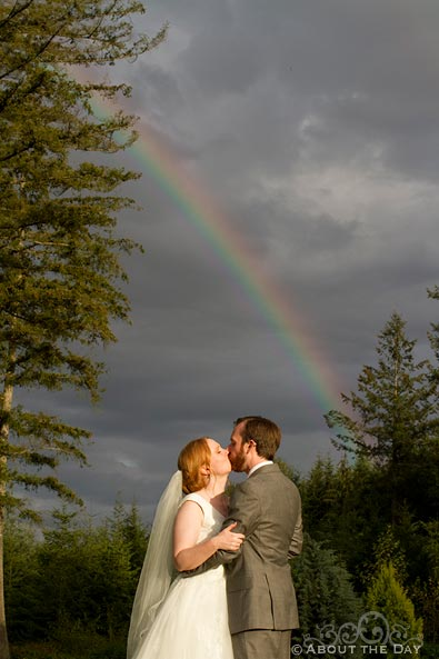 Bride and Groom kiss under a rainbow at Natures Connection in Arlington, Washington