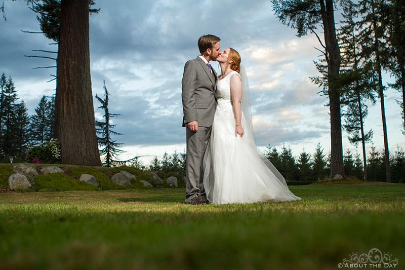 Dramatic sky for kissing Bride and Groomat Natures Connection in Arlington, Washington