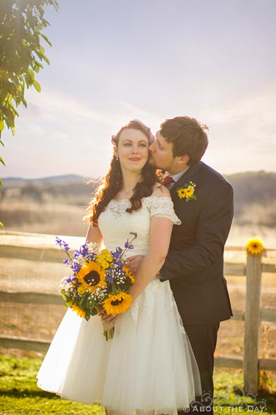 Bride and Groom with sunflowers and a white fence