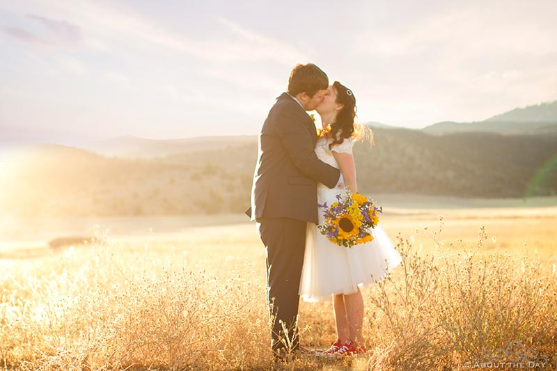 Bride and Groom kiss in the golden light of fading sun