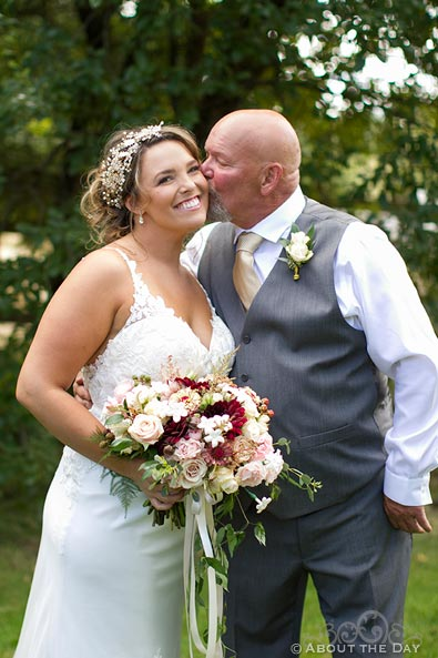 Father of the Bride kisses her on the cheek