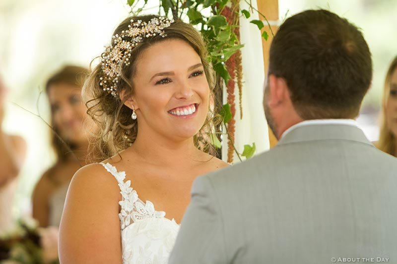 Beautiful bride looks on as Groom says his vows