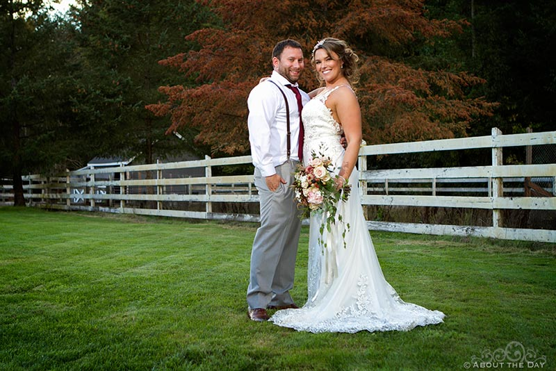 Bride and Groom pose in the field with a white fence