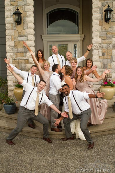 Wedding party gets crazy while the couple kisses