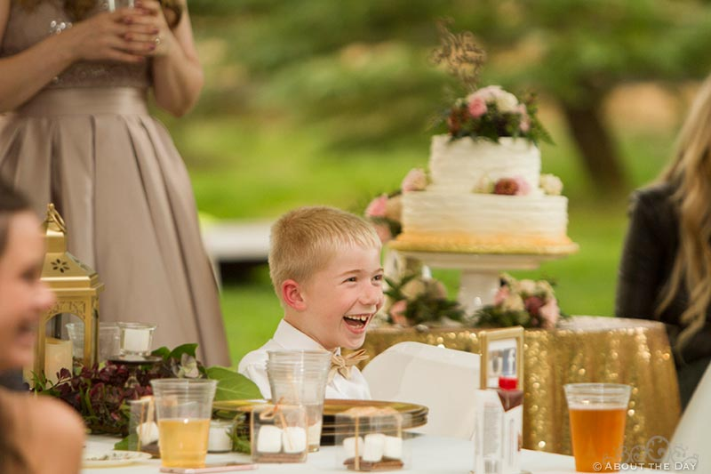 Ring bearer laughs at something during the speeches