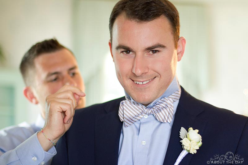 Best man adjusts grooms bow tie