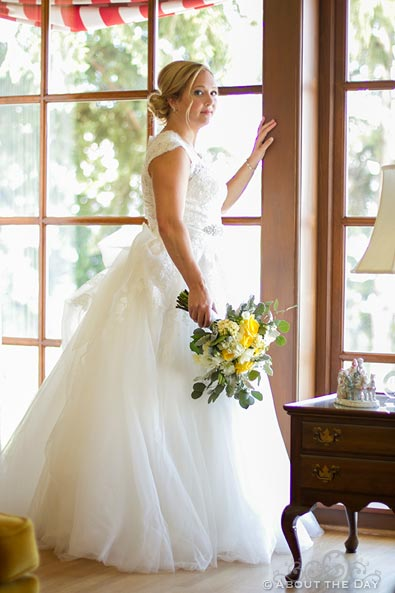 Stunning bride gazes out window with natural light