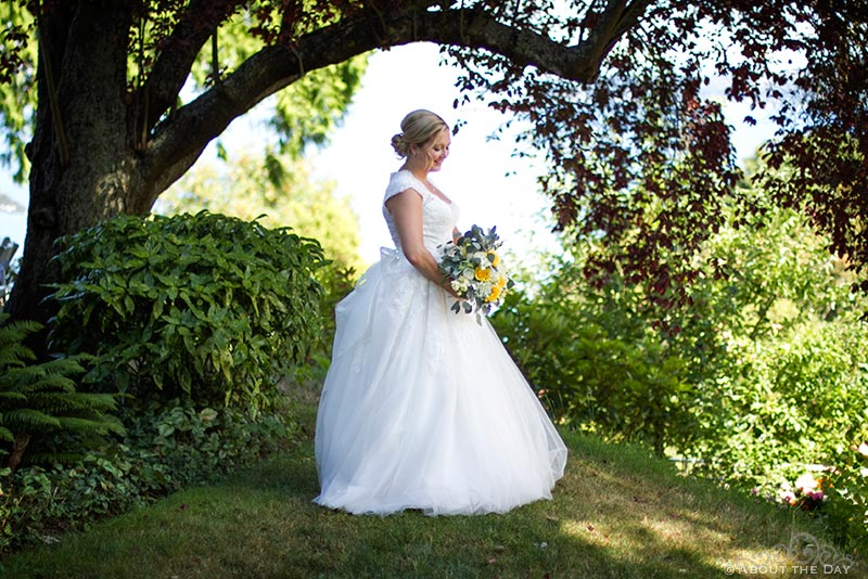 bride poses under a tree at her parents house
