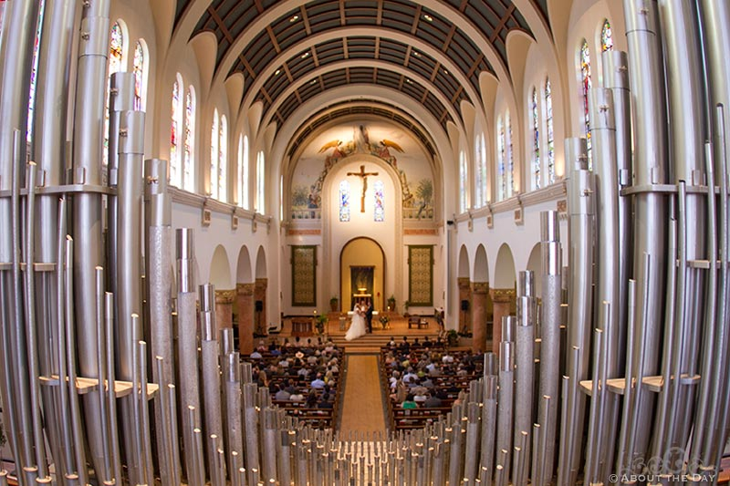 View of wedding ceremony through the organ at Holy Rosary Catholic Church in Seattle, Washington