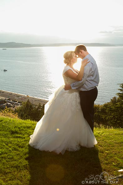 Bride and Groom snuggle as the sun sets over Puget Sound
