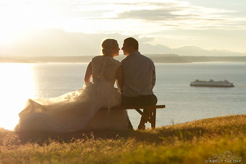 Bride and Groom snuggle as Seattle ferry goes by in the sunset