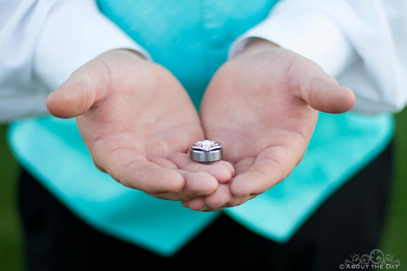 Best man holds out the rings with both hands