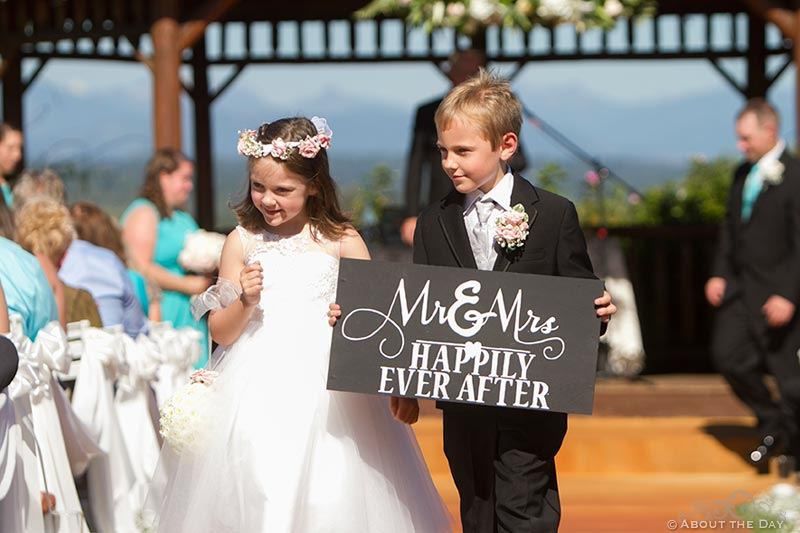 Kids hold sign while waking down the isle