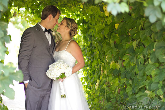 Bride and Groom kiss in the ivy tunnel