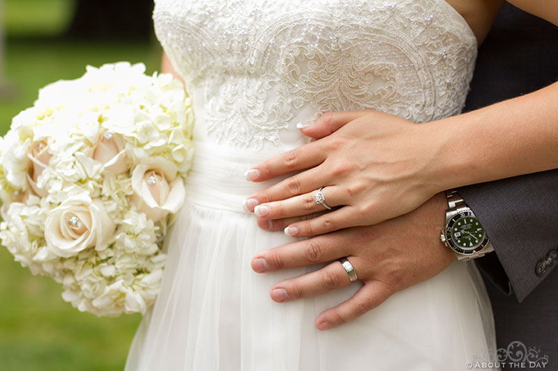 Bride and Groom hands, rings, and white flowers