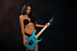Sexy girl plays a blue Ibanez guitar in boudoir shoot