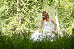 Bride walks through tall grass at Wallowa Lake in Joseph, Oregon