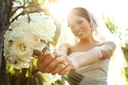 Bride holds her boquet out in front of her
