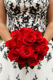 Red roses in front of a black and white wedding dress