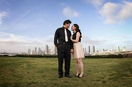 Engaged couple stands tall over San Diego skyline from Centennial Park