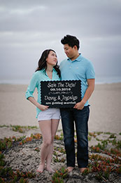 Engaged couple display their save the date sign