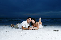 Engaged couple lays on Clearwater Beach at dusk