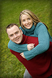 Engaged couple wear warm sweaters in bright colors