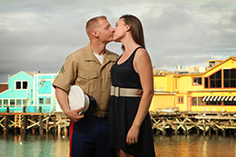 Engaged military couple kiss on Monterey Warf