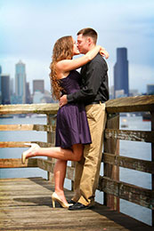 Engaged couple kiss with Seattle skyline in background