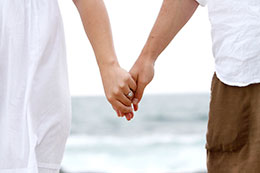 Engaged couple hold hands with beach in the back