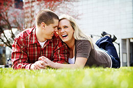 Engaged couple laughs on lawn in downtown Portland