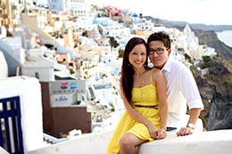 Couple poses with Oia in the background
