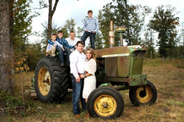 The Duke family poses on an old John Deere tractor