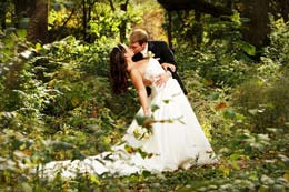 Groom kisses bride in the forest