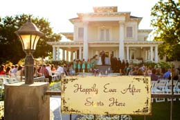 Wedding in the background of a happy sign at Moore Mansion