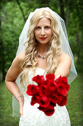 Sassy blonde Bride holds out her red roses