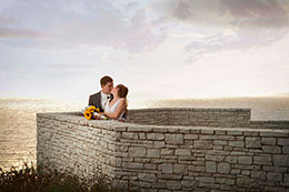Bride and Groom kiss behind a short brick wall over looking the ocean