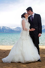 Bride and groom kiss on the beach of Lake Tahoe