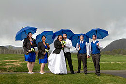 Wedding party with blue umbrellas in the rain